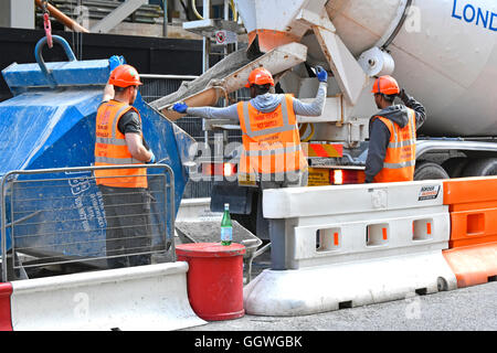 Labourer on City of London England UK building site helps delivery cement mixer truck reverse to crane hopper for - Stock Photo