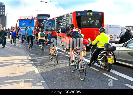 Rush hour on UK London Bridge as workers try to cycle home competing with other commuters & traffic in the scramble - Stock Photo