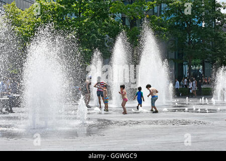 Children playing in variable height water fountain jets at random timings during hot summer weather ideal for kids - Stock Photo