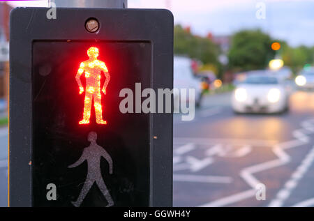 Red man at UK Pelican Crossing, with evening traffic in background - Stock Photo