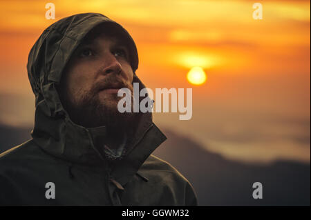 Man Traveler bearded face alone outdoor with sunset mountains on background Travel Lifestyle survival and emotions - Stock Photo