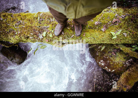 Feet Man standing on log over river outdoor Lifestyle Travel survival concept - Stock Photo