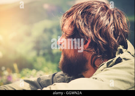 Young Man bearded relaxing alone outdoor Travel Lifestyle concept mountains nature on background Summer journey - Stock Photo