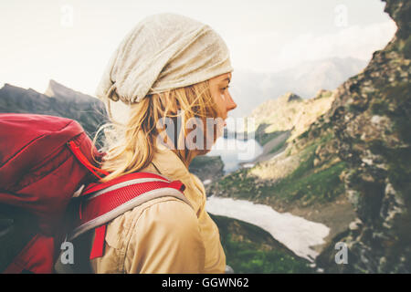 Young Woman with red backpack hiking alone Travel Lifestyle concept lake and mountains landscape on background Summer - Stock Photo