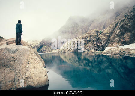Man Traveler standing alone on stone cliff lake and misty mountains on background Travel Lifestyle concept outdoor - Stock Photo