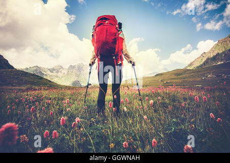 Woman Traveler with red backpack hiking Travel Lifestyle concept Summer vacations outdoor mountains and flowers - Stock Photo