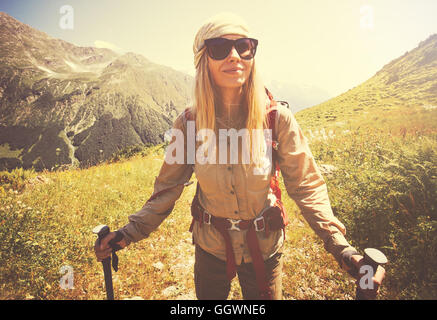 Happy Woman with backpack hiking Travel Lifestyle concept vacations outdoor mountains on background sunny day tone - Stock Photo