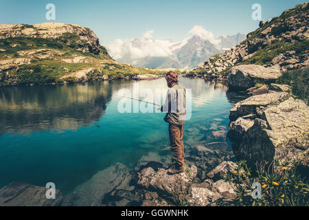 Young Man fishing on Lake with rod mountains landscape on background Travel Lifestyle concept summer vacations - Stock Photo