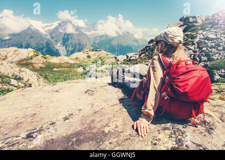 Woman Traveler with backpack admiring of mountains and clouds landscape Travel Lifestyle concept hiking adventure - Stock Photo