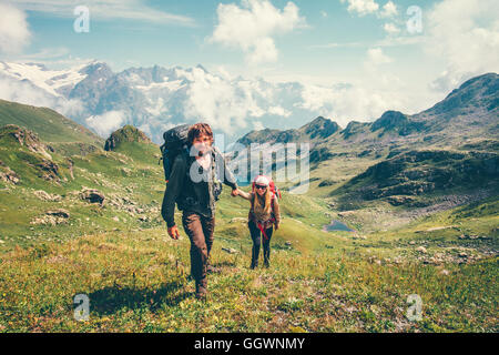 Happy romantic Couple Man and Woman Travelers with backpack holding hands mountaineering Travel Lifestyle and relationship love