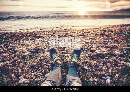 Woman Feet sneakers on beach sea sunset Travel Lifestyle Summer vacations trendy concept - Stock Photo