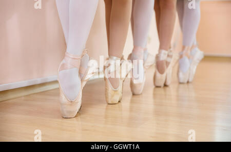 Legs of young ballerinas standing on pointe in row, ballet dancing class - Stock Photo