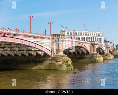 Blackfriars Bridge, giving road and pedestrian access over the River Thames, London, UK on a sunny day with blue - Stock Photo
