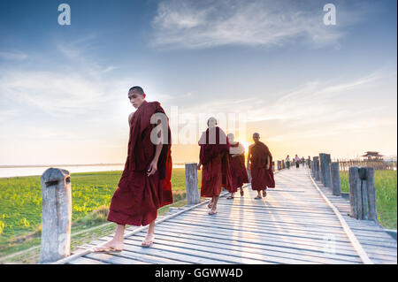 Buddhist monks sunset walk on U Bein bridge - Stock Photo