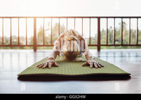 Woman doing stretching workout on fitness mat. Fitness female performing yoga on exercise mat at health club. - Stock Photo