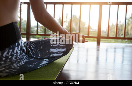 Close up of woman sitting on exercise mat with legs crossed and hands on knees. Female meditating in lotus pose - Stock Photo
