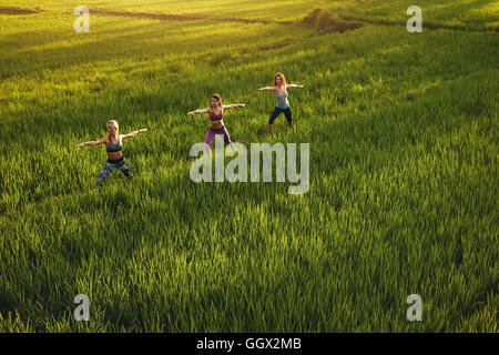Outdoor shot of yoga class in farm land. Young people doing yoga workout in farm. Three young women exercising in - Stock Photo