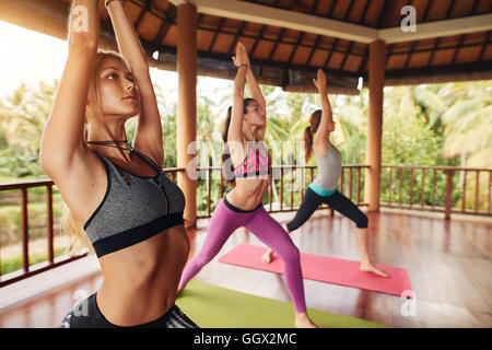 Three young woman doing yoga at class. Healthy group of female doing stretching workout with their hands joined - Stock Photo