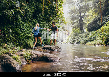 Couple climbing on rocks by mountain stream. Outdoor shot of young man and woman on hike. Man helping his girlfriend - Stock Photo