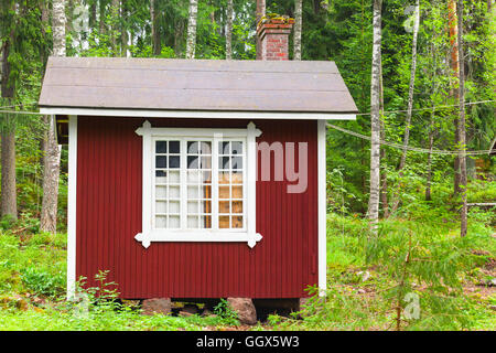 Small Scandinavian red wooden house over green forest background. Kotka, Finland - Stock Photo