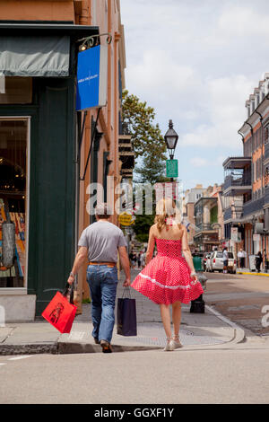 A man and a woman strolling through the French Quarter in New Orleans; the lady is wearing a red 1950s  petticoat - Stock Photo