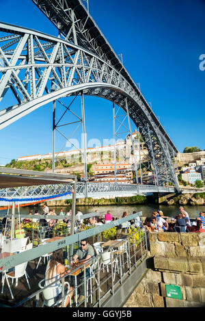 outdoor terrace bar cafe and landmark bridge in ribeira riverside area of porto portugal - Stock Photo