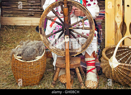 Near an old spinning wheel sits an elderly woman in national costume and worked on it, spinning. - Stock Photo