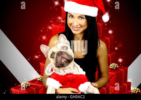 beautiful young woman and his dog wearing a Christmas costume - Stock Photo