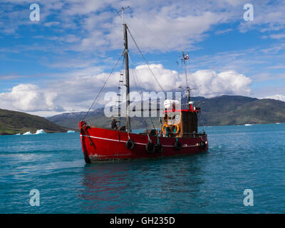 Small boat to take tourists to Qooroq Ice fjord Qassiarsuk Southern Greenland on a lovely sightseeing day with blue - Stock Photo