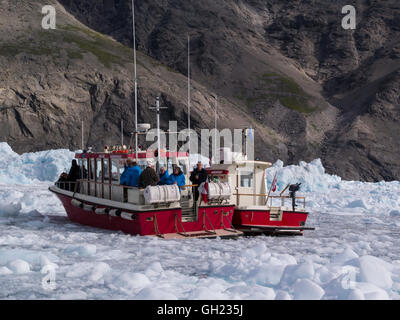 Small tourist boats sailing through icebergs of Qooroq Ice Fjord Tunulliarfik Fjord Southern Greenland fed by Greenland - Stock Photo