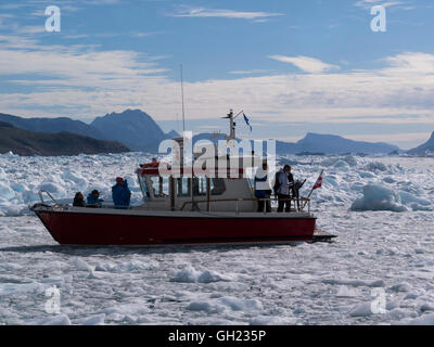 Small tourist boat sailing through icebergs of Qooroq Ice Fjord Tunulliarfik Fjord Southern Greenland fed by Greenland - Stock Photo