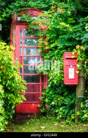 A public telephone kiosk and post box in a rural location overgrown by trees and shrubs - Stock Photo