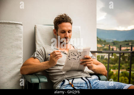 Young man sitting doing a crossword puzzle looking thoughtfully at a magazine, as he tries to think of the answer - Stock Photo