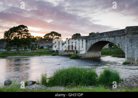 Stone bridge spanning River Wharfe as flows it through scenic Burnsall village, under dramatic summer evening red - Stock Photo
