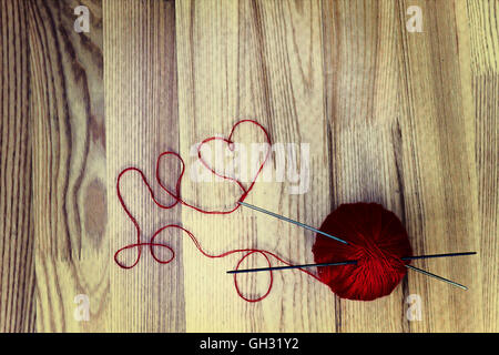Knitting concept. Wool ball and heart shaped thread on wooden background - Stock Photo