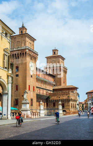 Cyclists crossing Corso Martiri della Liberta street with Estense castle in background. Ferrara, Italy. - Stock Photo