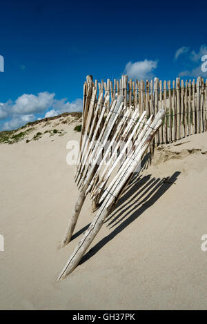 Sandy beach, blue sky with a worn wooden fence in the middle of the image, sunny day the fence casts shadows on - Stock Photo
