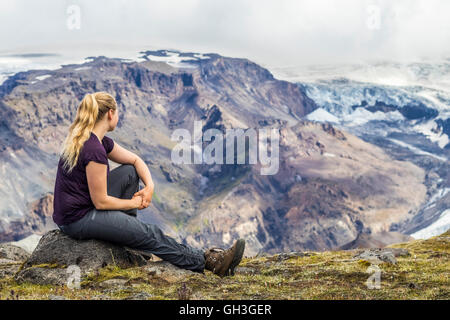 Young woman overlooking the mountains in Iceland. - Stock Photo