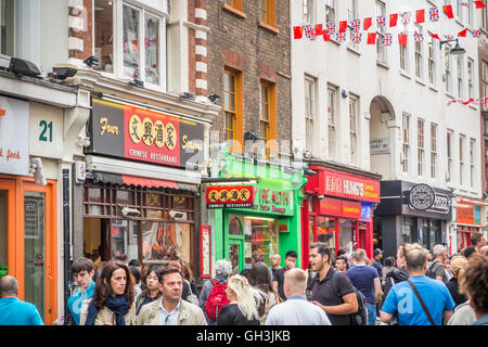 Bustling street scene with Chinese restaurants in Wardour Street, Chinatown, West End (Westminster), London, UK - Stock Photo