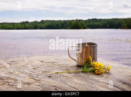 Stainless steel mug on stone near water on nature background - Stock Photo