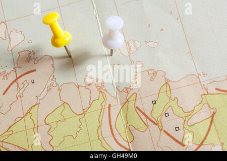 Push pins showing the location of a destination point on a map - Stock Photo