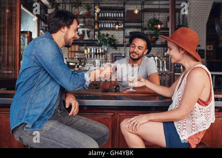 Portrait of young modern people sitting in the coffee shop and having their drinks. Group of friends at a cafe toasting - Stock Photo