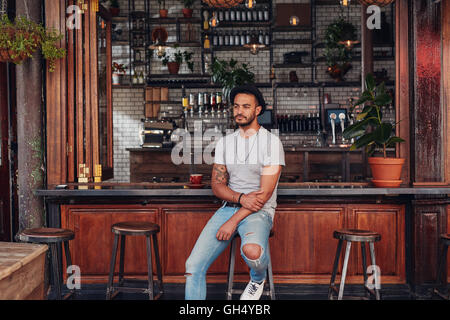 Portrait of upset young man sitting alone at a cafe counter. Modern young caucasian man looking serious. - Stock Photo