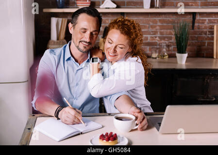 Woman looking how man writing - Stock Photo