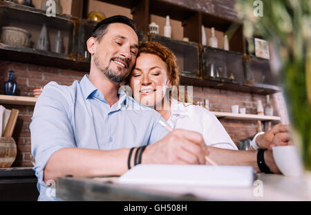 Woman looking how man taking notes - Stock Photo