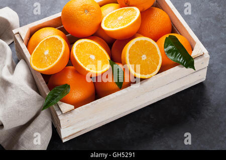 Fresh orange fruits in wooden box on stone table - Stock Photo