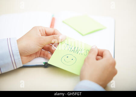 Hands of woman holding sticky note with Thanks text - Stock Photo
