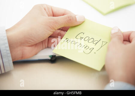 Hands holding sticky note with Good morning text - Stock Photo