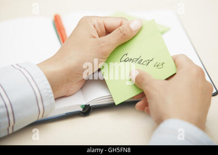 Hands holding sticky note with Contact us text - Stock Photo