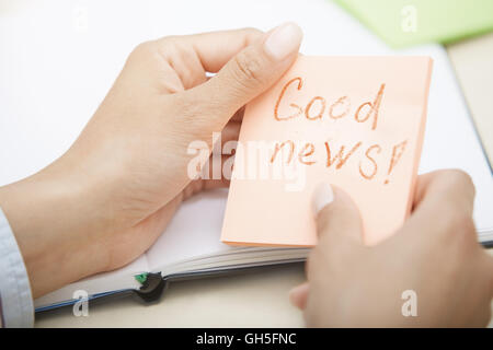 Hands holding sticky note with Good news text - Stock Photo